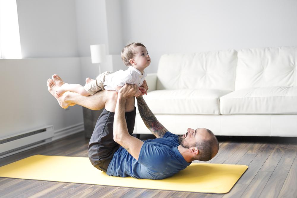 papa haciendo ejercicio con bebe en casa
