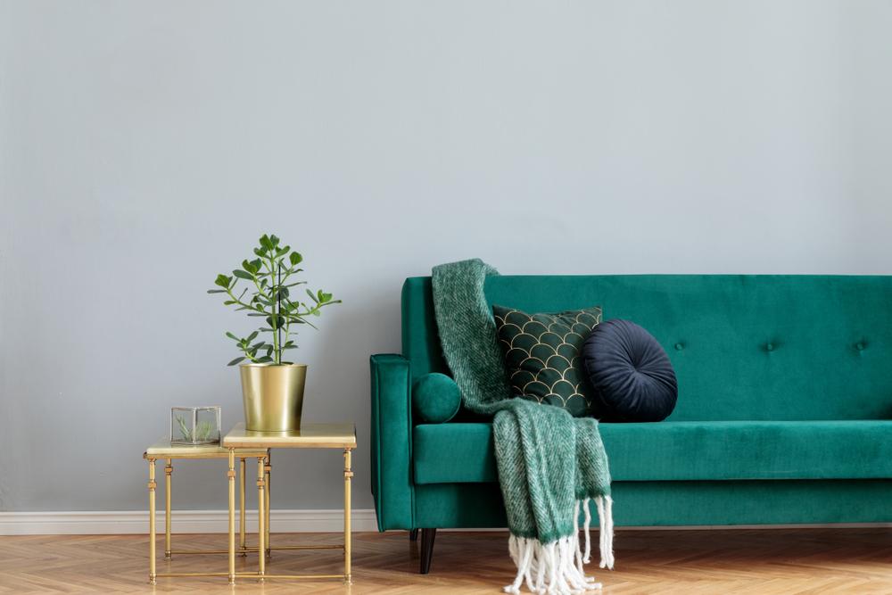 sofá de terciopelo verde con mesa dorada