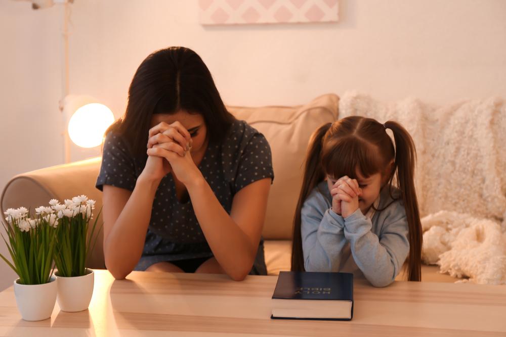 Madre e hija rezando en la sala
