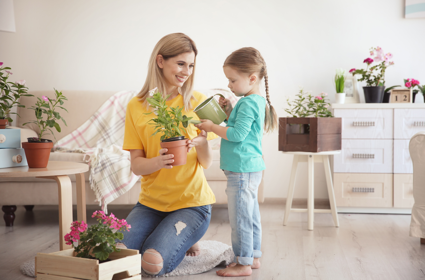 Mujer y niña regando planta y ahorrando agua