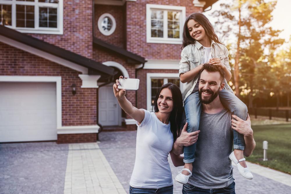 Familia con el celular fuera de la casa - subsidio de vivienda